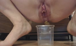 Shaved milf filled a cup with poop