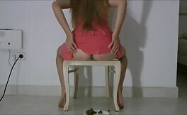 She's pooping from a wooden chair