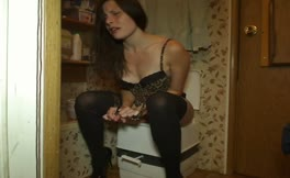 Dark haired babe shits over toilet